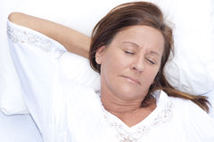 Relaxed mature woman asleep in bed. Portrait relaxed attractive mature woman asleep, resting in bed with closed eyes and smile on face, peaceful, happy Royalty Free Stock Photos