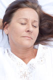 Relaxed mature woman asleep in bed. Portrait relaxed attractive mature woman lying asleep in bed with closed eyes and smile on face, peaceful, happy expression Stock Photos