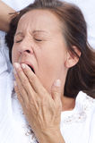 Tired mature woman yawning in bed Royalty Free Stock Photography