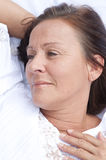 Relaxed mature woman resting in bed Stock Image