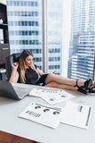 Portrait of relaxed female boss sitting at workplace with feet on table planning her workday writing goals in notebook stock image