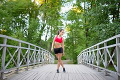 Portrait of relaxed fitness young woman on wooden bridge in park Stock Photos