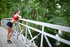 Portrait of relaxed fitness young woman on wooden bridge in park Royalty Free Stock Photo