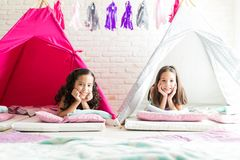Relaxed Girls With Hands On Chin Smiling In Teepee Tents. Portrait of relaxed girls with hands on chin smiling in teepee tents at home royalty free stock image