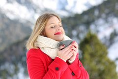 Relaxed lady breathing and holding coffee in winter. Portrait of a relaxed lady breathing fesh air and holding a coffee mug in a snowy mountain in winter royalty free stock image
