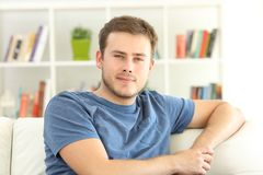 Portrait of a relaxed man at home. Portrait of a relaxed man looking at you sitting on a sofa at home royalty free stock photos