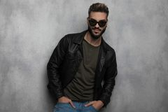 Portrait of relaxed man wearing leather jacket and sunglasses smiling. While standing on light grey wallpaper background royalty free stock image
