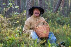 Portrait of relaxed mature man sitting in the forest with basket. stock images