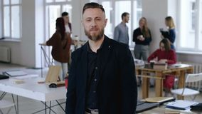 Portrait of relaxed middle aged Caucasian sales business coach man in black formal suit looking at camera at office. Handsome bearded confident male finance stock video footage