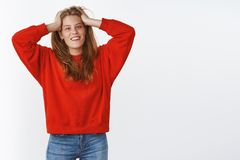 Portrait of relaxed outgoing good-looking young white female in stylish red sweater holding hands on head carefree. Playing with hair smiling joyfully liking royalty free stock images