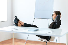 Portrait of relaxed pretty business woman. Sitting with legs on desk in the office Royalty Free Stock Images