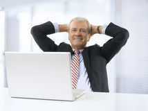 Portrait of relaxed senior businessman sitting in office. Royalty Free Stock Photos