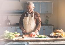 Calm mature houseman cutting vegetables and enjoying song. Portrait of relaxed senior man preparing healthy lunch in kitchen. He is listening to music form Stock Photo