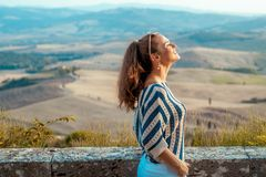 Relaxed stylish traveller woman in front of scenery of Tuscany. Portrait of relaxed stylish traveller woman in striped blouse in the front of scenery of Tuscany stock images