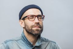 Portrait of relaxed unshaven male with closed eyes wears glasses, keeps eyes closed, enjoys calm atmosphere, isolated over white b stock images