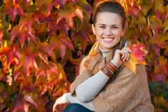 Portrait of relaxed woman with autumn leafs in front of foliage Royalty Free Stock Image