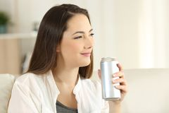 Woman holding a soda can looking away at home Stock Image