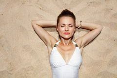 Portrait of relaxed woman in swimsuit laying on the sand Royalty Free Stock Images