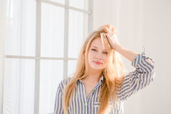 Portrait of relaxed woman with tousled hair. Portrait of relaxed pretty young woman with tousled hair in striped pajamas Stock Images