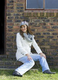 Portrait of relaxed woman in winter's clothing seated on barn steps of farm. Stock Photos
