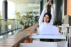 Portrait of relaxed young Asian business woman sitting and raising hands over head in office. Stock Photo