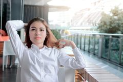 Portrait of relaxed young Asian business woman sitting and touch head with hands in office. Sunshine effect. Portrait of relaxed young Asian business woman Stock Photos