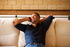 Relaxed young black man talking on mobile phone with hand behind his head Stock Photography