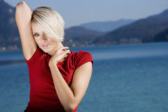 Relaxed young blond woman. Portrait of relaxed young blond woman with blue sea or lake in background Stock Image