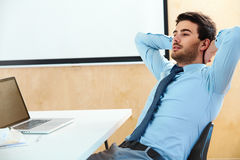 Portrait of a relaxed young businessman sitting in a bright office Stock Image
