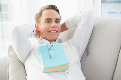 Portrait of a relaxed young man with book lying on sofa Stock Images