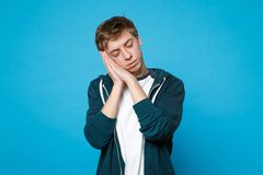 Portrait of relaxed young man in casual clothes keeping eyes closed, resting, sleaping with hands near face isolated on stock photography