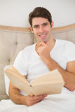 Portrait of relaxed young man reading book in bed Stock Images