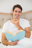 Portrait of relaxed young man reading book in bed. Portrait of a relaxed young man reading book in bed at house Stock Images