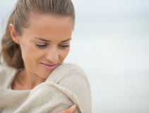 Portrait of relaxed young woman on cold beach royalty free stock image