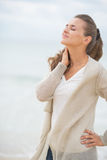 Portrait of relaxed young woman on cold beach Royalty Free Stock Photography
