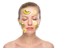 Portrait of relaxed young woman making fruits mask Stock Photography
