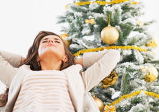 Portrait of relaxed young woman near christmas tree Royalty Free Stock Images