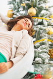 Portrait of relaxed young woman sitting near christmas tree Stock Images