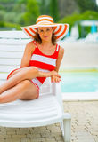 Portrait of relaxed young woman sitting on sunbed Stock Photos