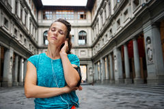 Portrait of relaxed young woman in sportswear listening mp3. Now it is time to invest in your body and no matter you are at hometown or traveling. Relaxed woman stock images