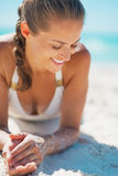 Portrait of relaxed young woman in swimsuit laying on beach Royalty Free Stock Photos