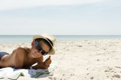 Portrait of relaxing boy in hat and glasses on beach. Profile portrait of teenager boy in hat on beach Royalty Free Stock Photos