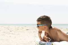 Portrait of relaxing boy in hat and glasses on beach. Profile portrait of teenager boy in hat on beach Royalty Free Stock Photo