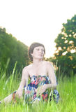 Portrait of Relaxing Caucasian Brunette Woman Posing Outdoors on Nature Background at Sunset Stock Photo