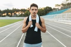 Portrait of a relaxing fitness man with towel on shoulders. Young smiling man with towel on shoulders posing at camera on stadium after morning workout. Portrait Royalty Free Stock Image