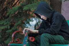 Portrait of relaxing teenager looking at skateboard in his hands Royalty Free Stock Images