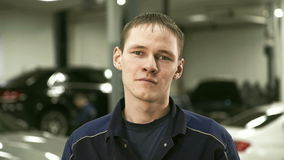 Portrait of repairman on a background of car service center. stock footage