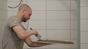 A portrait of a repairman who smears glue over the surface of the tile stock video footage