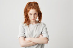 Portrait of resentful young pretty redhead girl looking at camera brutally with crossed arms over white background. royalty free stock image