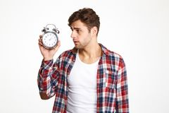 Portrait of a restless troubled man. Portrait of a restless man holding and looking at alarm clock isolated over white background royalty free stock images